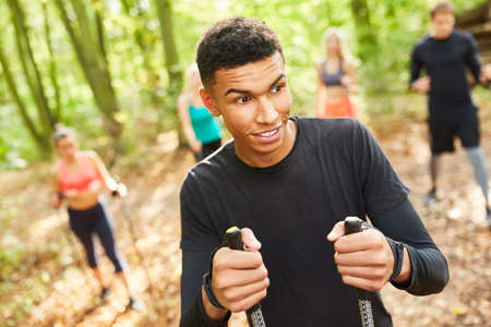Young man doing nordic walking with friends as fitness and endurance training