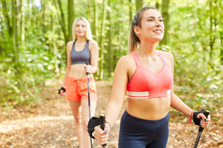 Two friends doing Nordic Walking in nature for endurance and health Imagens