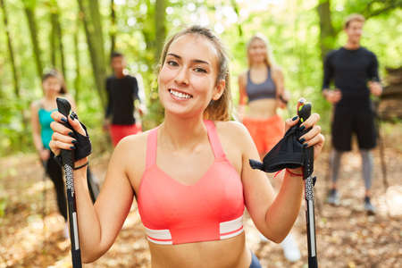 Young woman as fitness trainer in park with nordic walking course in nature in summer Imagens