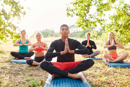 Group of young people enjoying a zen meditation in yoga class in the nature in summer