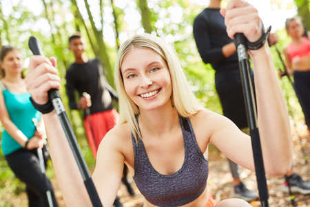 Young woman as a fitness trainer with group while Nordic walking in nature in summer