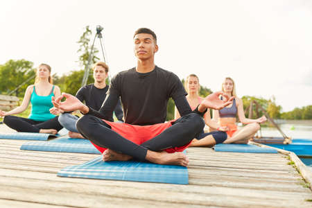 Group of friends in the lotus position enjoying a zen meditation in a lakeshore yoga class Imagens