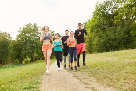Group of friends as a team jogging for fitness and health in nature