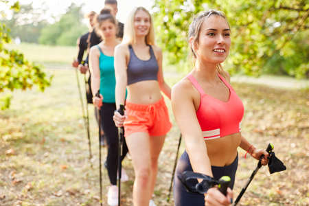 Friends as a Nordic walking group training in nature in summer Imagens