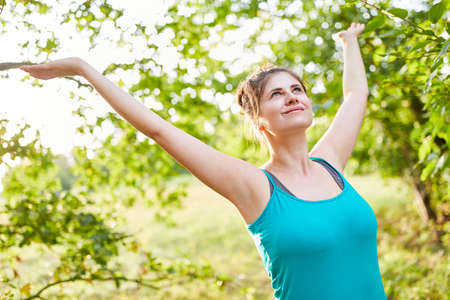 Young woman stretching and breathing fresh air in nature as an antistress exercise Imagens