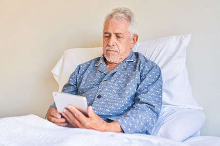 Senior man as patient in bed in hospital with tablet computer reading an email