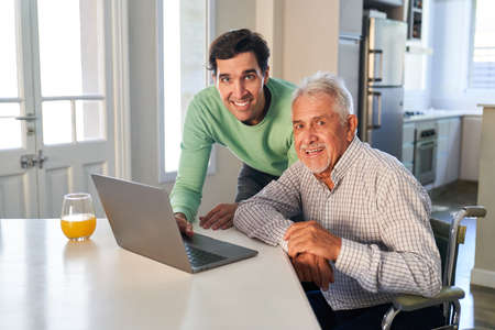 Young man and senior have fun on laptop computer in apartment or retirement home