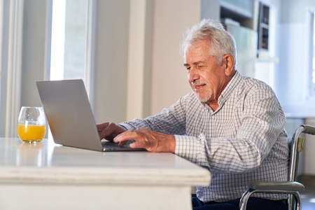 Senior at home using laptop computer is typing email or chatting online with family