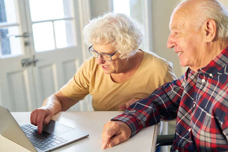 Senior couple having fun on laptop computer while chatting on social media at home