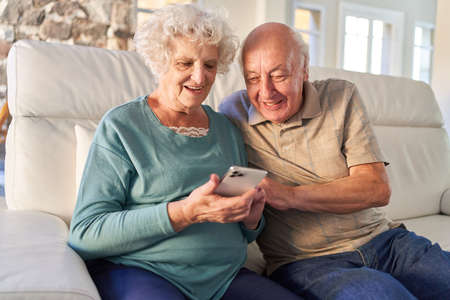 Senior couple with smartphone has fun video chat or reading a text message