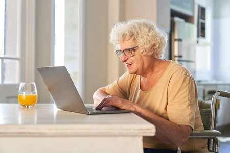 Happy senior citizen in a wheelchair at the computer online while video chat or on social media