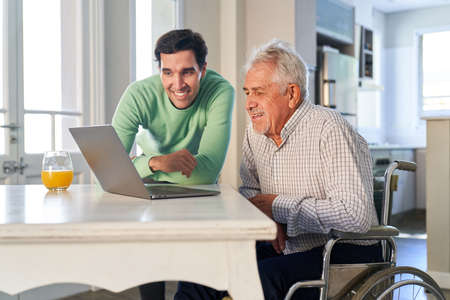 Curious senior and young man on laptop computer while video streaming or video chat