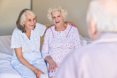 Two senior women as best friends on the bed in the hospital or nursing home