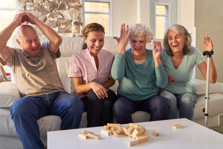 Happy seniors in family play at game night at home Imagens