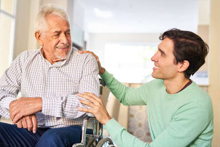 Caring man taking care of senior father in wheelchair in retirement home or at home