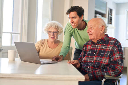 Seniors learn to chat and communicate online on the laptop computer with the help of their son