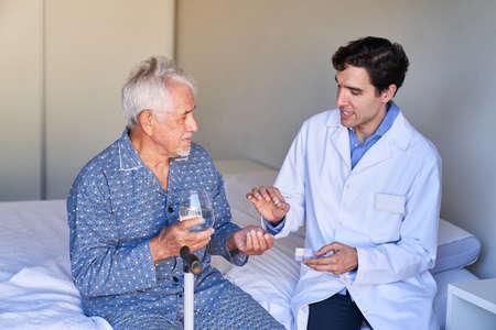 Doctor or nurse gives senior patient a tablet in hospital or nursing home
