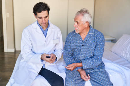 Male nurse sits with blood glucose meter next to a senior on a hospital bed