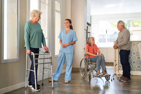 Group seniors with disabilities and a nurse in a retirement home or nursing home