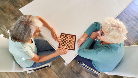 Two retired senior women playing checkers as a leisure activity at home
