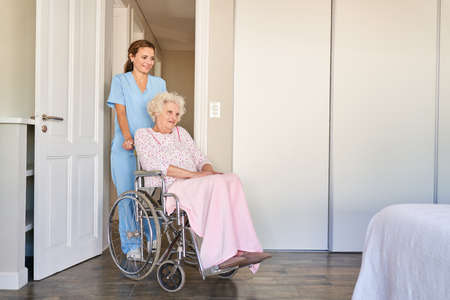 Elderly care worker pushes senior citizen in wheelchair in nursing home or old people's home Imagens