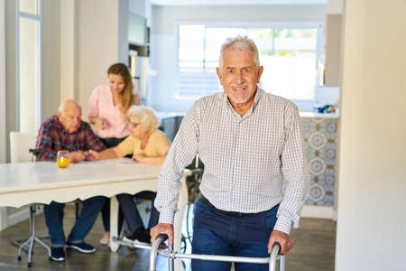 Satisfied senior after stroke with walking aid or rollator in a nursing home Imagens