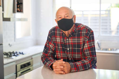 Senior with face mask because of  and in his apartment in the kitchen