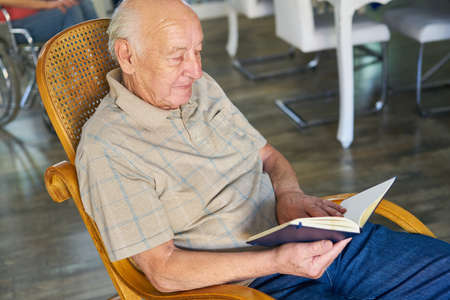 Retired senior relaxes reading a book at home or at the retirement home