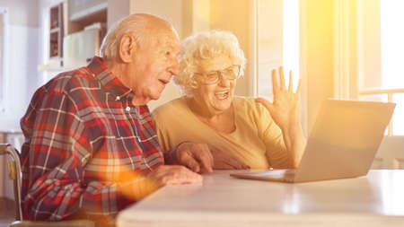 Couple of seniors waving to family while video chat on laptop computer online
