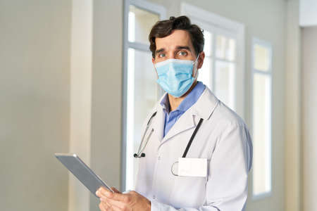 Young doctor with face mask because of  and and with tablet computer Imagens