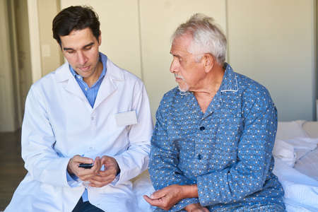 A geriatric nurse checks the blood sugar level of a senior with diabetes on the measuring device
