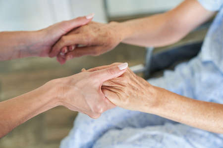 Hands of nurse hold hands of elderly woman as a symbol of comfort and support