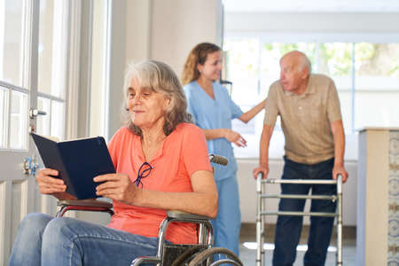 Senior patient in a wheelchair reads a book in the retirement home or rehab clinic Imagens