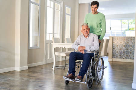 Satisfied senior citizen in a wheelchair looked after by his son in home care or in a retirement home
