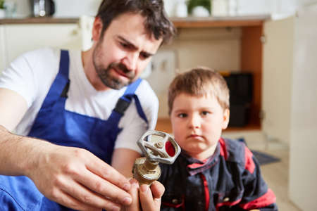 Father and son look at a shut-off valve to repair the broken kitchen sink