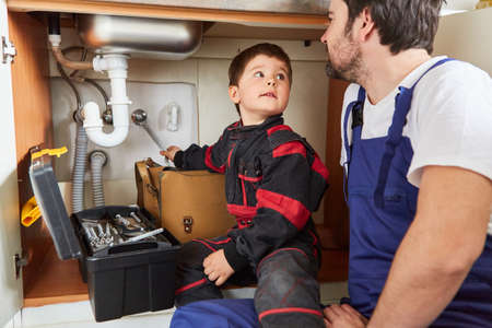 Father and son work together to repair the broken sink in the kitchen as do-it-yourselfers