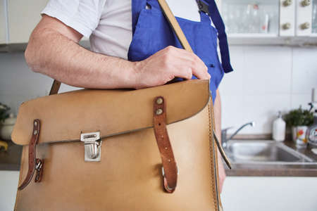 Plumber handyman with tool bag in the kitchen as a repair emergency service Imagens
