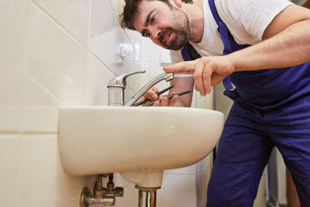 Plumber handyman repairing a defective tap on the sink in the bathroom