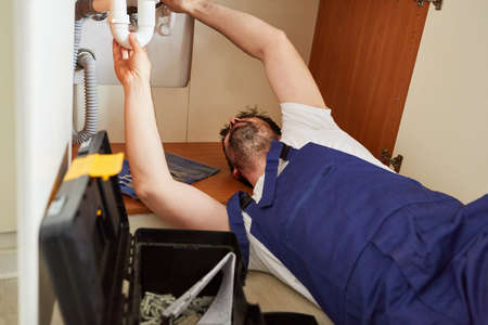 Do-it-yourselfers or plumber from the emergency service repairs a defective siphon in the kitchen sink