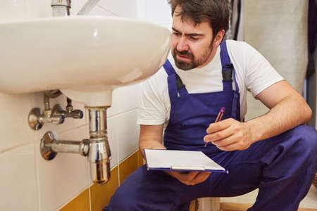 Plumber with checklist on clipboard after repairing siphon on sink