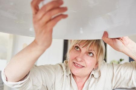 Handyman woman changes LED lightbulb on energy-saving lamp at home Imagens