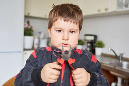 Little boy holding pliers while handyman or handyman play in the kitchen Imagens