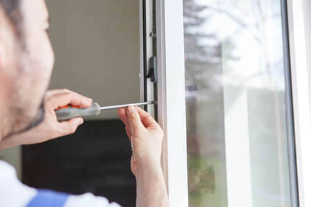 Craftsmen from specialist companies install and adjust windows in an apartment