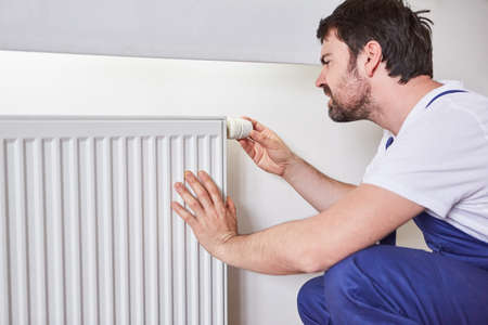 Installer or do-it-yourselfer adjusts the thermostat on the radiator of a heating system
