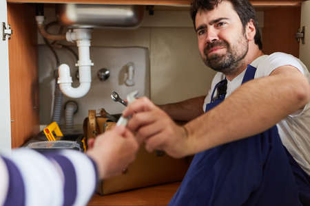 A stressed handyman needs help repairing the sink in the kitchen Imagens