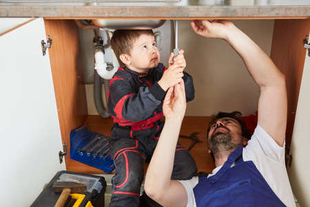 As do-it-yourselfers, father and son repair the broken sink in the kitchen together