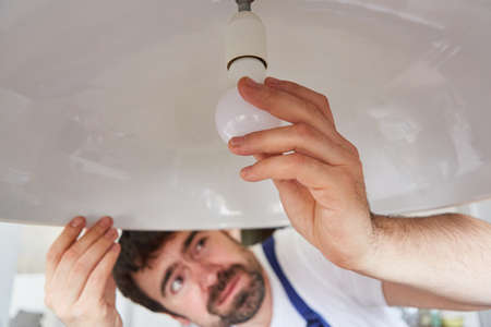Do-it-yourselfers or craftsmen exchanges defective lightbulbs on the ceiling lamp