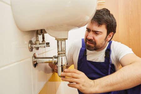 Plumber repairman repairs siphon on sink in bathroom Imagens