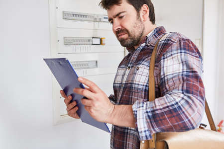 Electrician in front of the fuse box looks at clipboard with checklist for the test Imagens