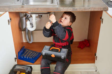 Child as a handyman with a toolbox repairing a broken sink
